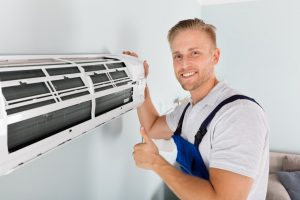 handyman fixing air conditioning unit