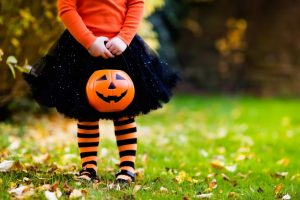 a little girl dressed up as a witch while holding a jack-o-lantern