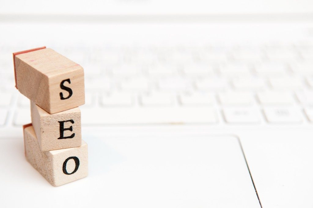 wooden blocks read seo on top of a laptop